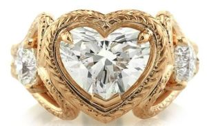 This stunning ring features a bold, faceted, heart shaped diamond on top, in a romantic, detailed frame, and two heart frames centered with diamonds on the sides. Available from MarkBroumand.com.